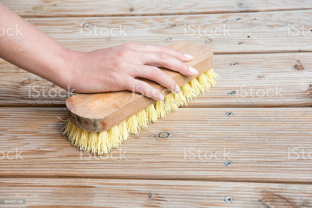 Female Hand scrubbing wooden deck stock photo