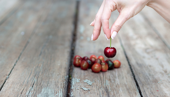 Female hand selecting a cherry