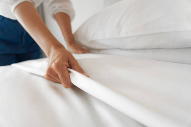 female hand set up white bed sheet in bedroom - maid stock pictures, royalty-free photos & images