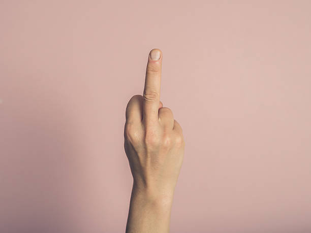 female hand showing rude gesture - swearing stockfoto's en -beelden