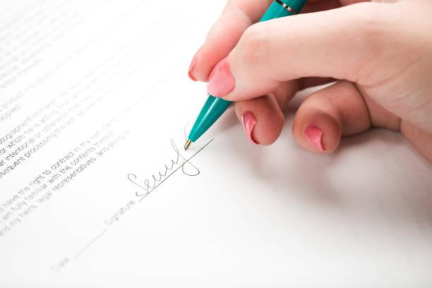 femme main signer un contrat. - titre mondial photos et images de collection