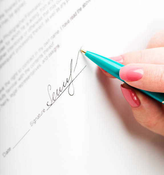 female hand signing a contract. - world title stock photos and pictures
