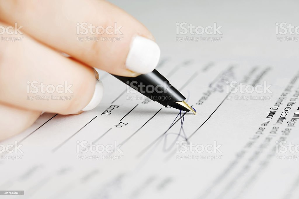 Female hand signing contract royalty-free stock photo