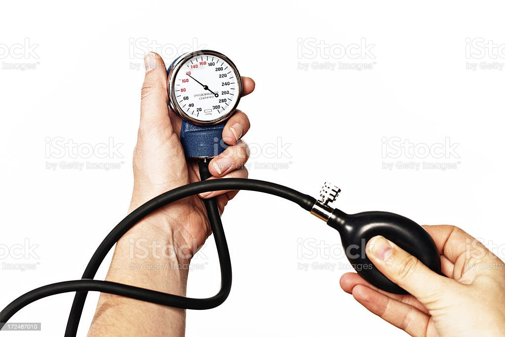 Female hand squeezes bulb of blood pressure gauge, holding dial royalty-free stock photo