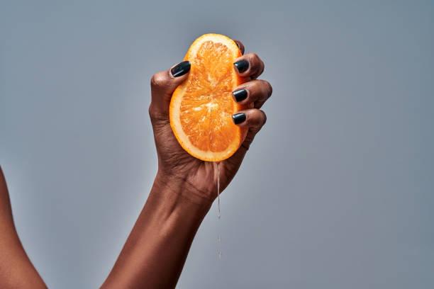 Female hand squeezing orange isolated on grey stock photo