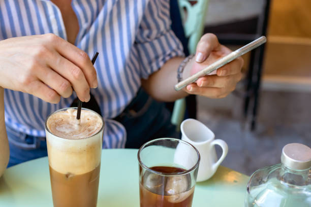 Female hand stirring a straw on a greek cold coffee, freddo cappuccino, outdoors stock photo