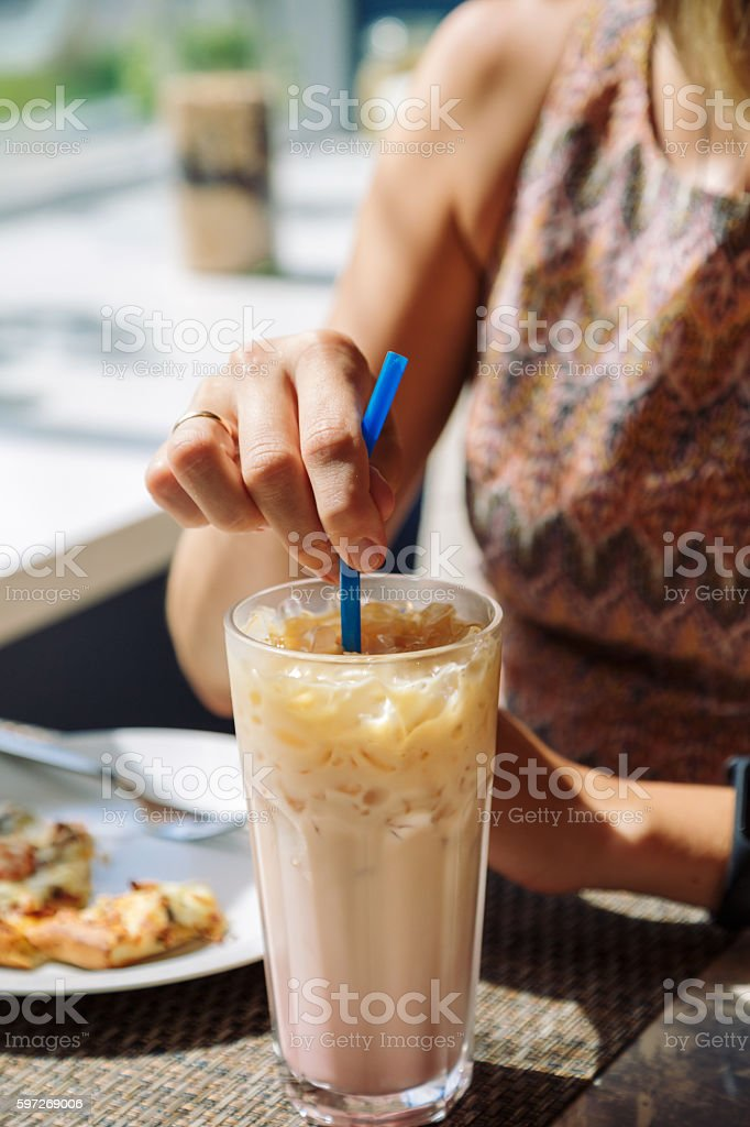 Female hand stirring cold drink in glass with straw photo libre de droits
