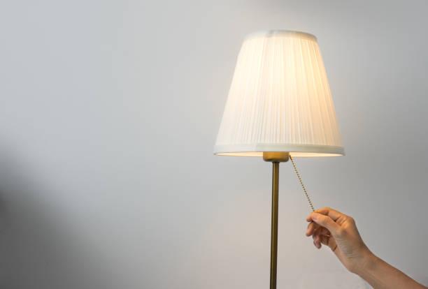main femme allumer la lampe de table. - lampe électrique photos et images de collection