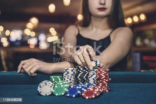 Female hand taking poker chips from pile