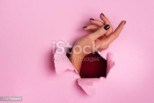 istock Female hand through torn pink paper background. Geasture concept 1147535653