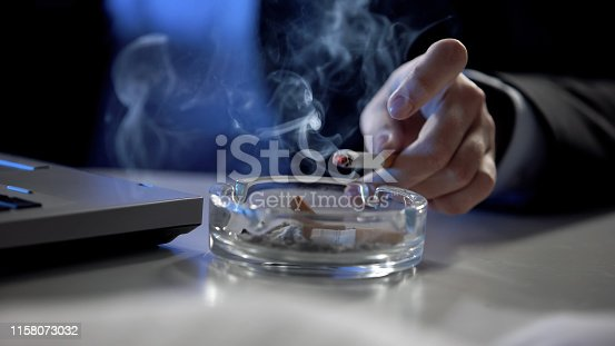 istock Female hand throwing cigarette ash in tray, smoking at workplace, stressful job 1158073032