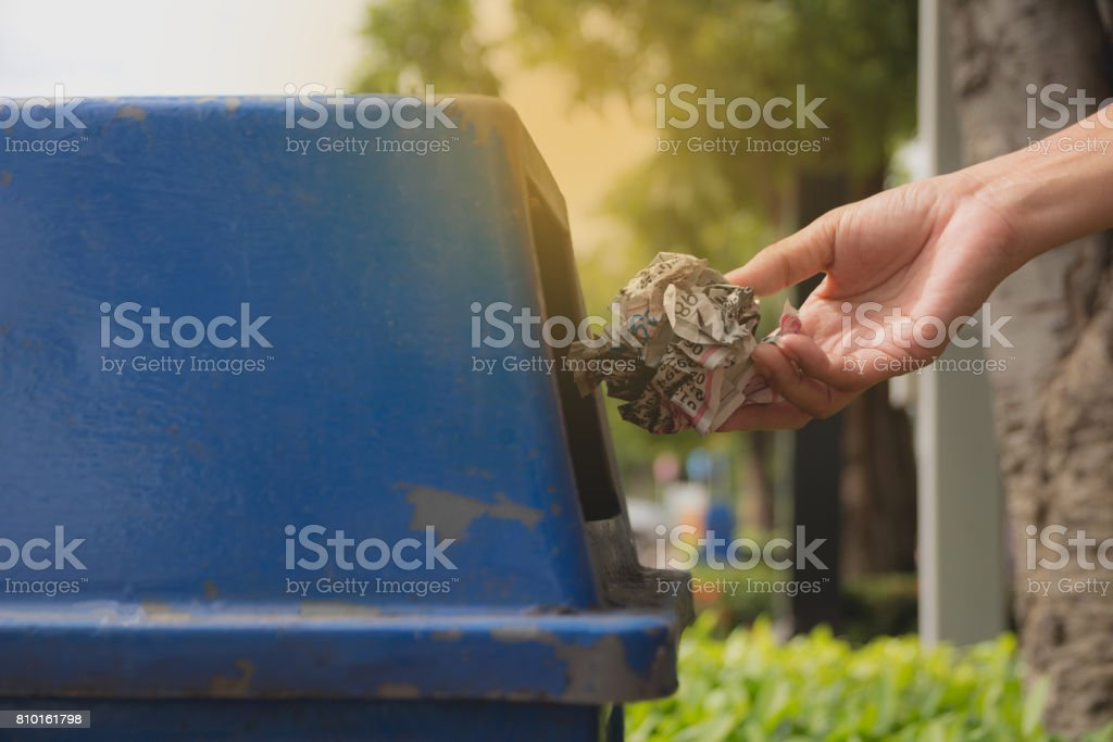 Mano femenina lanza papel arrugado en papelera de plástico azul. - foto de stock