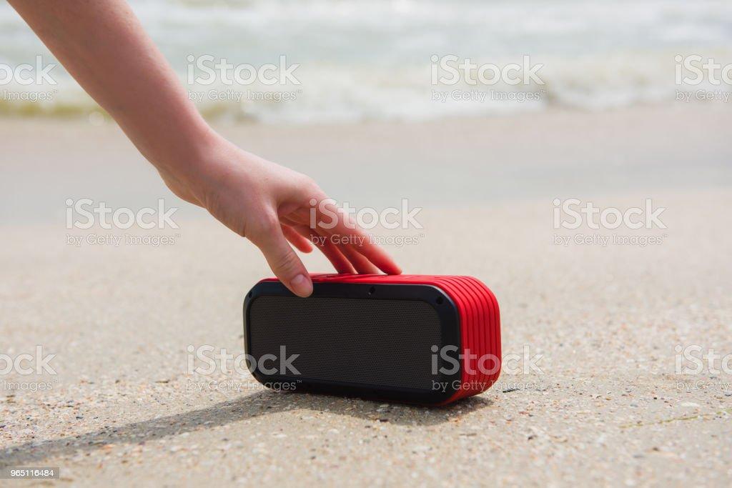 Female hand touch portable speaker stock photo