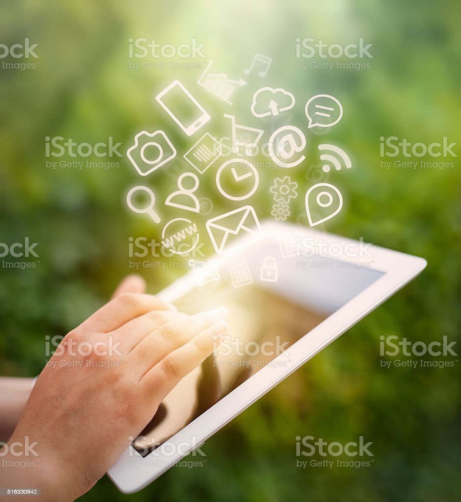female hand touching tablet computer screen and app icons fly stock photo