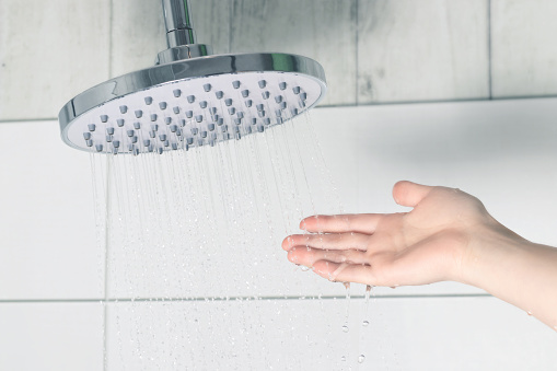 Female hand touching water pouring from a rain shower head, checking water temperature