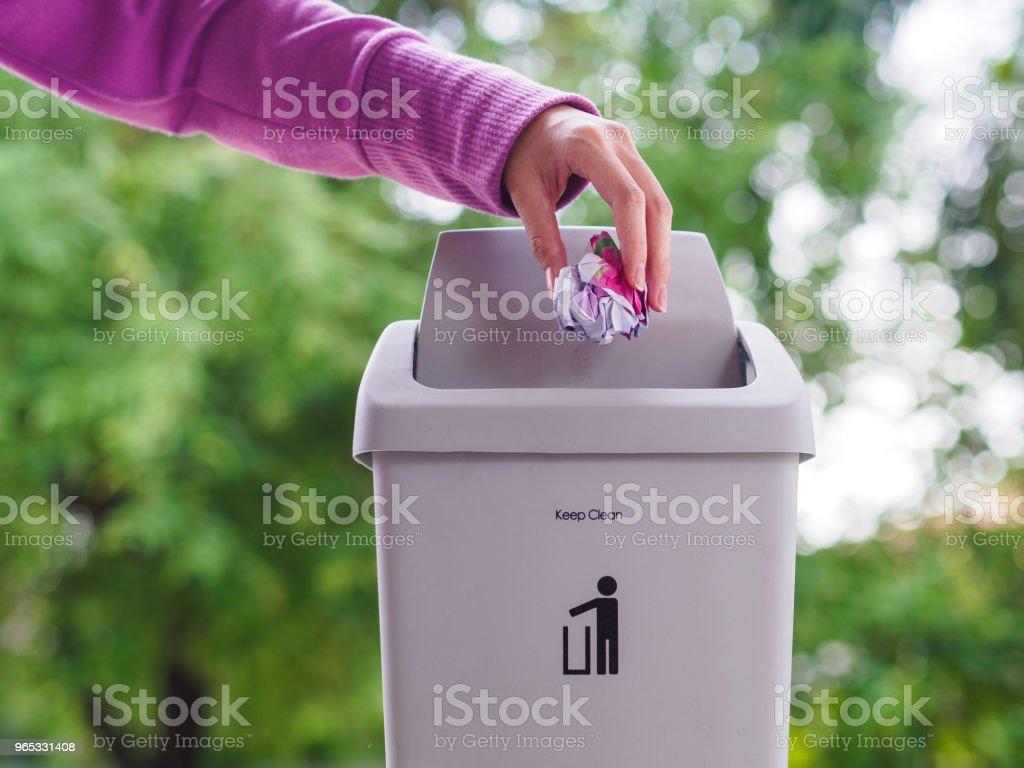 女性手 trowing 一張紙到散景背景的垃圾桶裡。清潔概念。 - 免版稅乾淨圖庫照片
