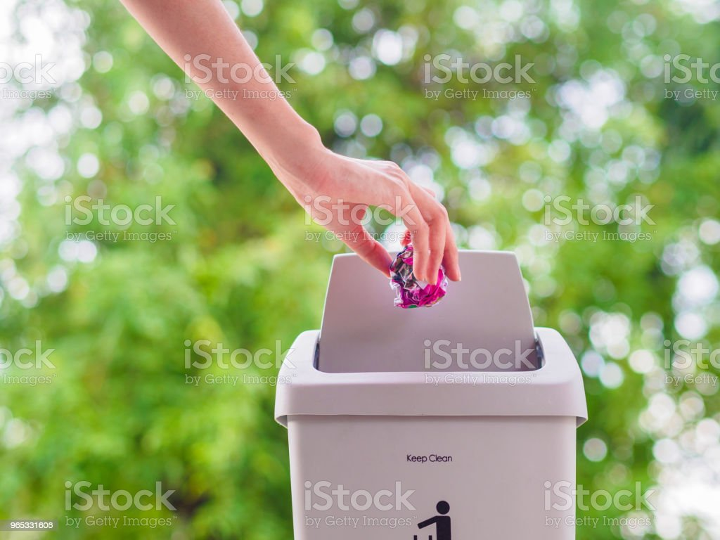 female hand trowing a paper into a garbage bin on bokeh background. cleaning concept. royalty-free stock photo