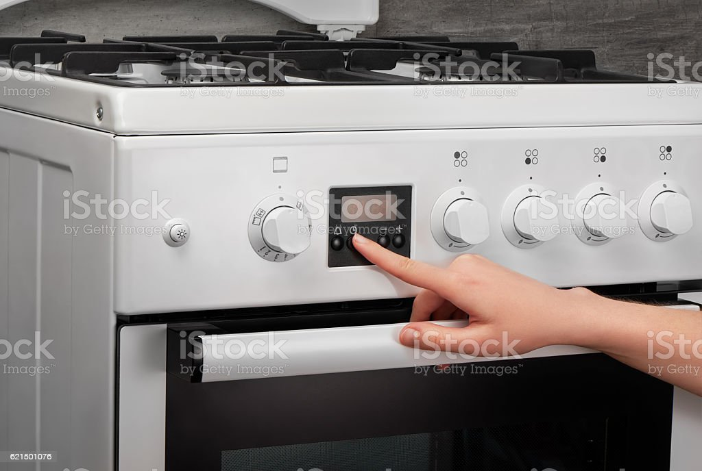 Female hand turning on white kitchen gas stove on gray Lizenzfreies stock-foto