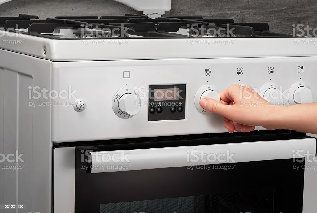 Female hand turning on white kitchen gas stove on gray photo libre de droits