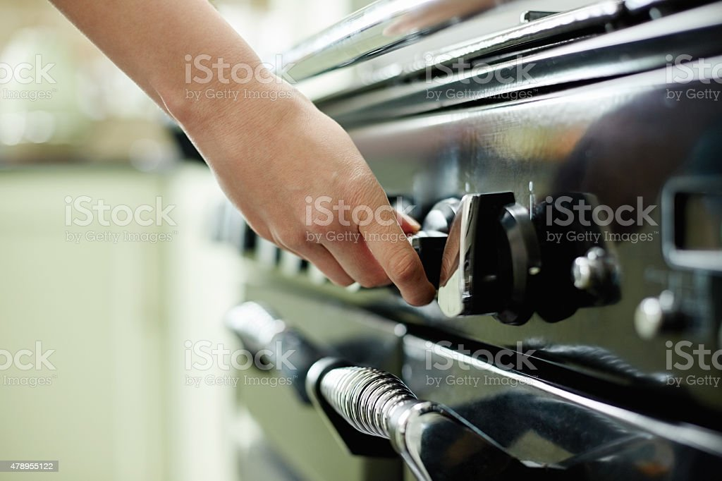 Female hand turning stove controller stock photo