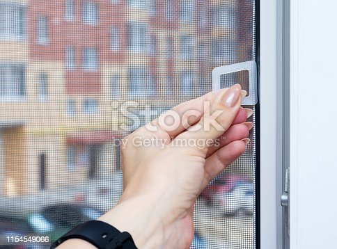 Female hand uses PVC window with a mosquito screen or fly screen mesh against the background of the street. Protection against insects. Close-up, selective focus.