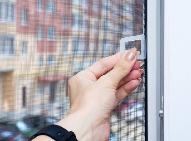 vrouwelijke hand maakt gebruik van pvc-venster met een mug scherm of vliegen scherm mesh tegen de achtergrond van de straat. bescherming tegen insecten. close-up, selectieve focus. - gaas stockfoto's en -beelden