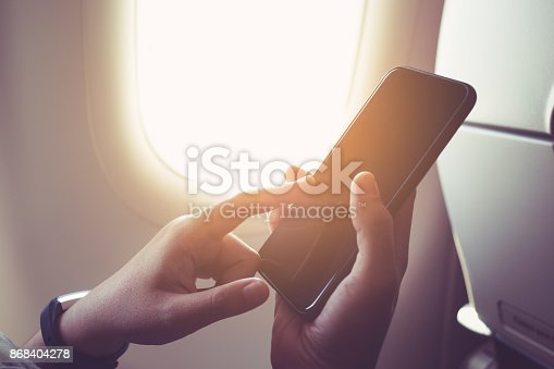 Female hand using smartphone on plane with window.Business technology and travel concepts ideas
