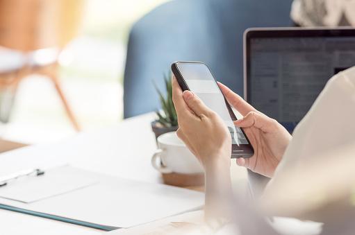 Mano Femenina Con Smartphone Mientras Trabajaba En El Escritorio En La Oficina Foto de stock y más banco de imágenes de Actividades bancarias