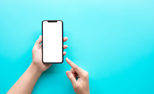 Female hand using smartphone with blank screen on color background.technology and connectivity concepts