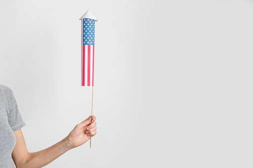 Female hand with a firework rocket over white background
