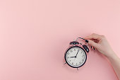 istock Female hand with alarm clock. Morning concept 1127294832