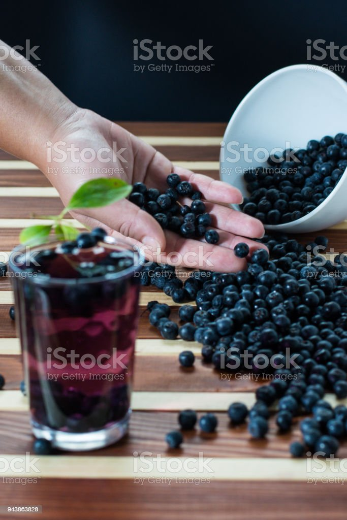 Female hand with aronia and glass of aronia juice stock photo