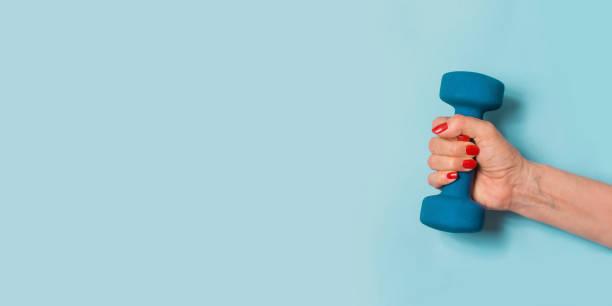 weibliche hand mit blau hantel auf blau. sport-konzept. wellness. - trainingsplan frauen stock-fotos und bilder