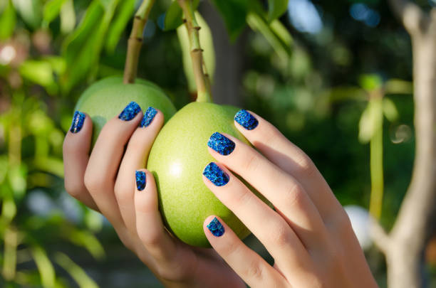 Female hand with blue nail art stickers stock photo