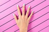 女性手と爪のブルーにピンクの背景