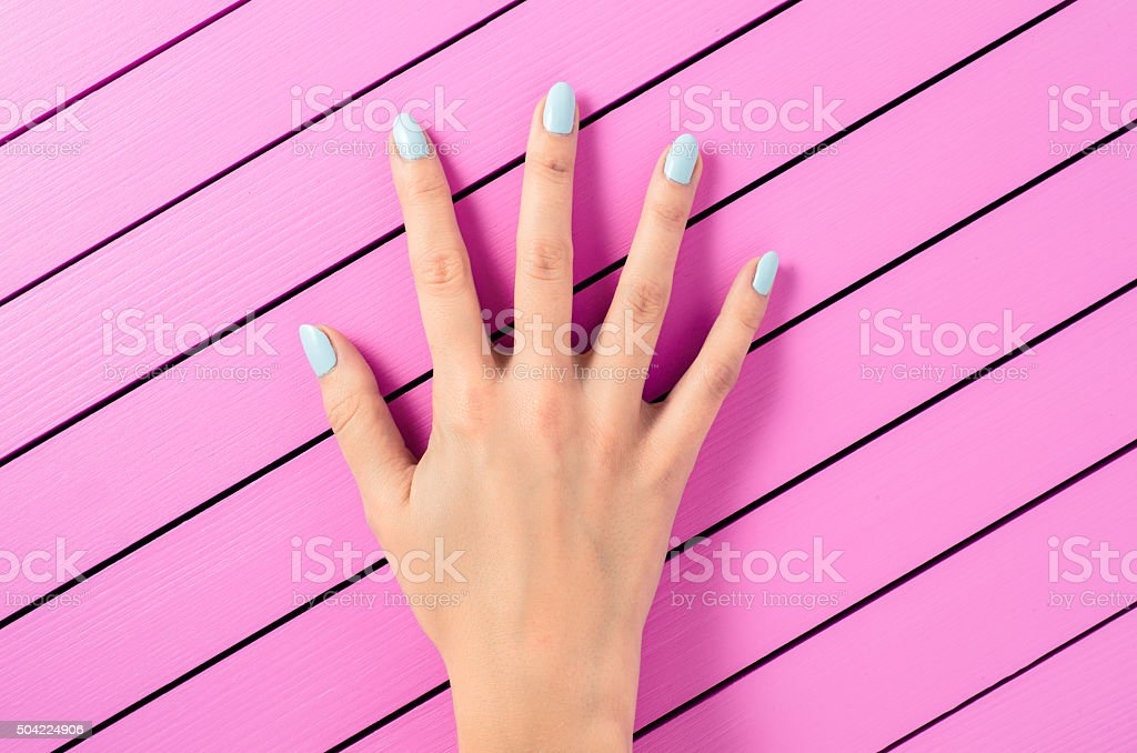 Female hand with blue nails over pink background stock photo