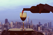 Female hand with bottle pours red wine into glasses on blurred San Francisco city background. Service on the roof of the restaurant