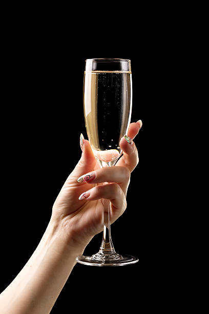 Female hand with champagne glass on black background. Female hand with champagne glass on black background. sergionicr stock pictures, royalty-free photos & images