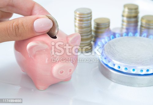 istock Female hand with coin and piggy bank near the flame of a gas stove in the kitchen. Symbolic image of cost, energy efficiency and saving natural gas at home. 1174994693