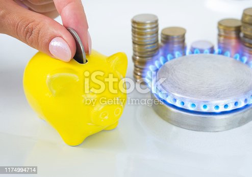 istock Female hand with coin and yellow piggy bank near the flame of a gas stove in the kitchen. Symbolic image of cost, energy efficiency and saving natural gas at home. 1174994714