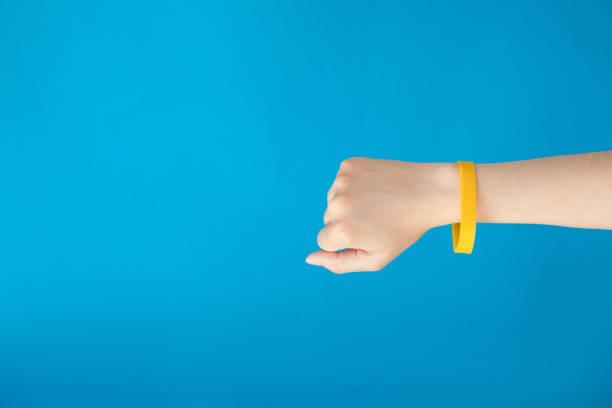female hand with empty yellow bracelet on blue background.  clear sweat band mock up design. - браслет стоковые фото и изображения