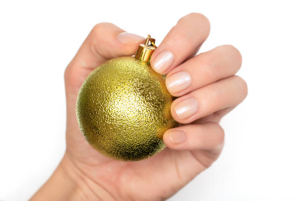 Female hand with glitter nail design holding christmas ball stock photo