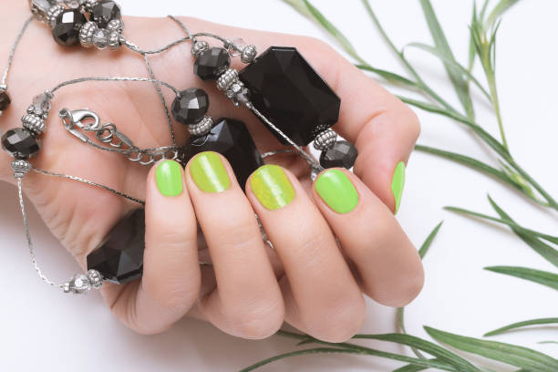 Female hand with green neon nail design on white background. stock photo