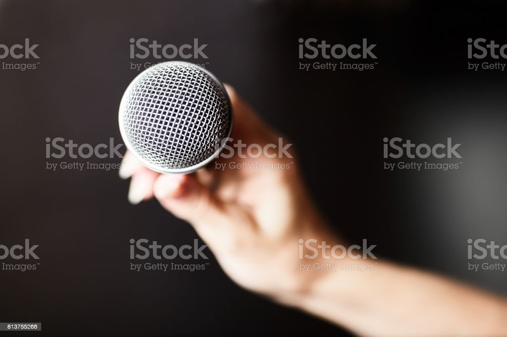 Female hand with microphone on background stock photo