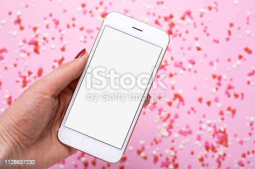 istock Female hand with mobile phone on background with pink and red hearts 1128637232
