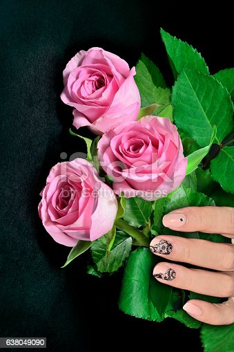 1147741037istockphoto Female hand with nail art manicure and pink roses 638049090