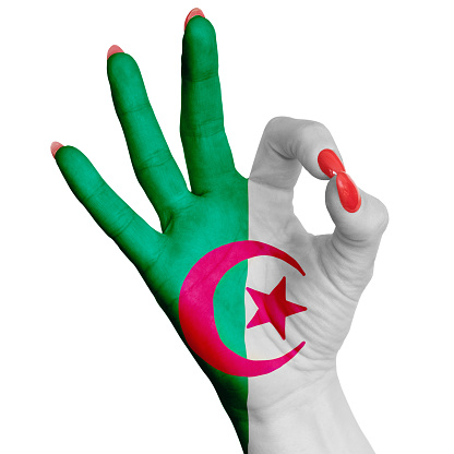 Female hand with ok gesture in color national flag of algeria as a symbol of victory. For tourism and tourist advertising, positive political, cultural, social management of the country