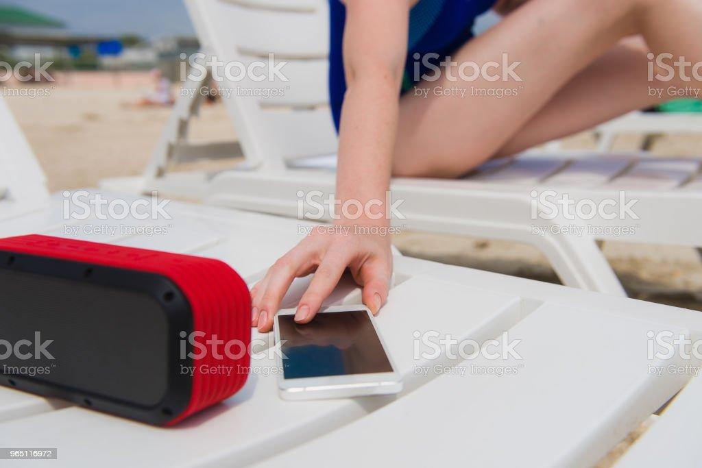 Female hand with phone and speaker at beach zbiór zdjęć royalty-free