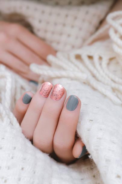 weibliche hand mit rosa und grauen nageldesign - herbst nagellack stock-fotos und bilder