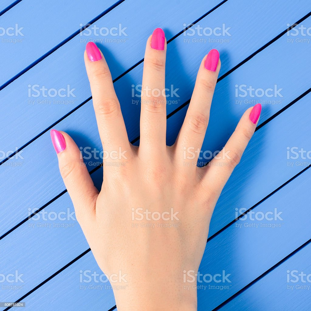 Female hand with pink nails on blue wooden background stock photo